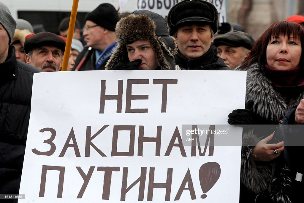 People hold a sign reading '' No to Putin's laws'' as they attend an opposition rally to protect rights of freedom of assembly and public activities in St. Petersburg on February 10, 2013.