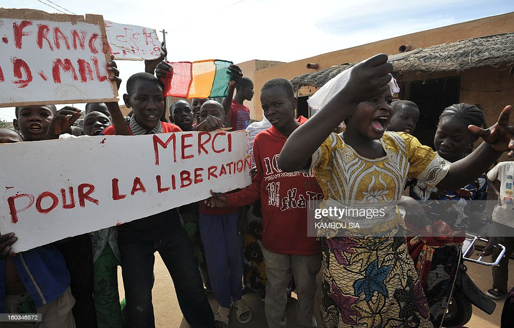People hold a sign reading 'Thank you for the liberation' on January 29, 2013 in Ansongo, a town south of the northern Malian city of Gao, as Niger troops enter the city. Troops from Niger and Mali on January 29 entered Ansongo, which along with Gao was recaptured by French-led soldiers over the weekend in a lightning offensive against radicals holding Mali's north. So far, just 2,000 African troops have been sent to Mali or neighboring Niger, many of them from Chad, to boost the French-led offensive which began on January 11 and led to the recapture of several towns, including Ansongo.