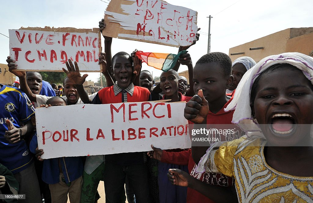 People hold a sign reading 'Thank you for the liberation' on January 29, 2013 in Ansongo, a town south of the northern Malian city of Gao, as Niger troops enter the city. Troops from Niger and Mali on January 29 entered Ansongo, which along with Gao was recaptured by French-led soldiers over the weekend in a lightning offensive against radicals holding Mali's north. So far, just 2,000 African troops have been sent to Mali or neighboring Niger, many of them from Chad, to boost the French-led offensive which began on January 11 and led to the recapture of several towns, including Ansongo. AFP PHOTO / KAMBOU SIA