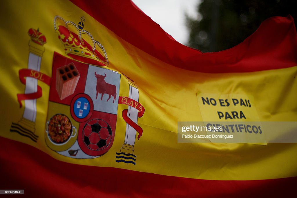 People hold a Spanish flag reading 'This is not a country for scientists' during a demonstration against R&D cuts for sciences on September 27, 2013 in Madrid, Spain. Young Spanish scientists have called for a demonstration during the European Researchers' Night under the header, 'No Sciences, No Future', in response to cutbacks in research and development for Sciences. They claim that many Spanish researchers are leaving the country to find a jobs.