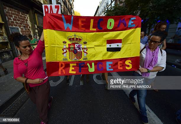 People hold a Spanish flag welcoming refugees during a rally in support of migrants and refugees as part of the European Day of Action in Madrid on...
