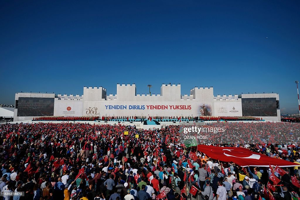People hold a Turkish national flag during a rally to mark the 563rd anniversary of the conquest of Istanbul by Ottoman Turks on May 29, 2016 in Istanbul. / AFP / OZAN