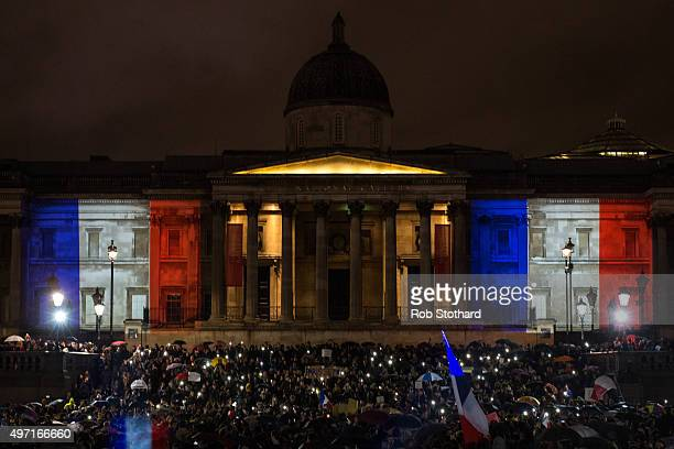 People hold a vigil for victims of the Paris terrorist attacks in Trafalgar Square on November 14 2015 in London England Several landmarks across...