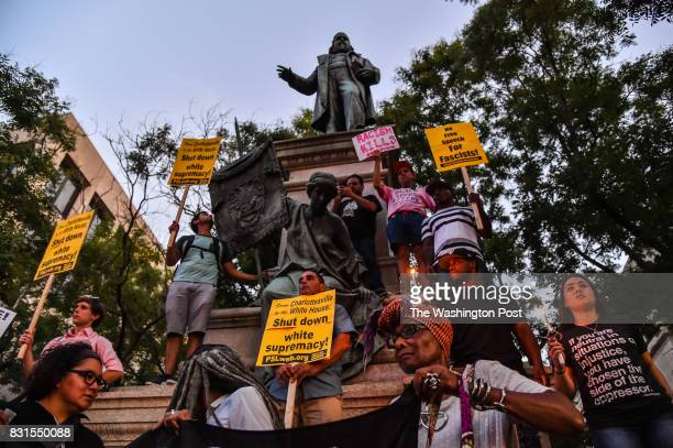 People hold a vigil in front of the statue of Albert Pike a Confederate general at Judiciary Square on Sunday August 13 in Washington DC a day after...