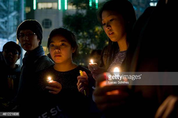 People hold a vigil organized by the International Federation of Journalists for the victims of the terrorist attack on 'Charlie Hebdo' in Paris at...