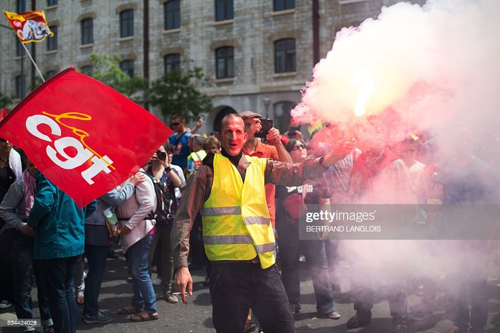 People hold aloft smoke flares as they take part in a demonstration against the French government's planned labour law reforms in front of Les Terrasses du Port commercial centre on May 26, 2016 in Marseille. / AFP / BERTRAND