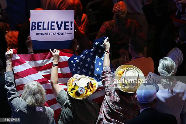 People hold an American flag during the final day of the Republican National Convention at the Tampa Bay Times Forum on August 30 2012 in Tampa...