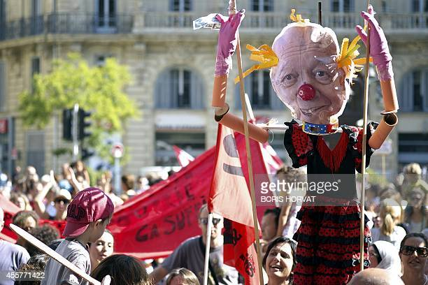 People hold an effigy of Marseille's mayor JeanClaude Gaudin as parents and their children demonstrate in front of Marseille's city hall on September...