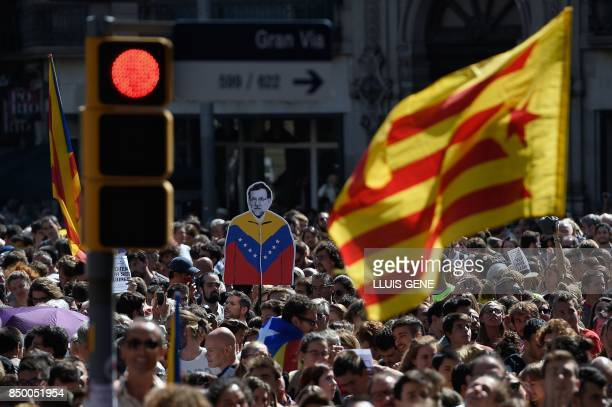 People hold an 'Estelada' and a placard depecting Spanish Prime Minister Mariano Rajoy man during a protest in Barcelona on September 20 2017...