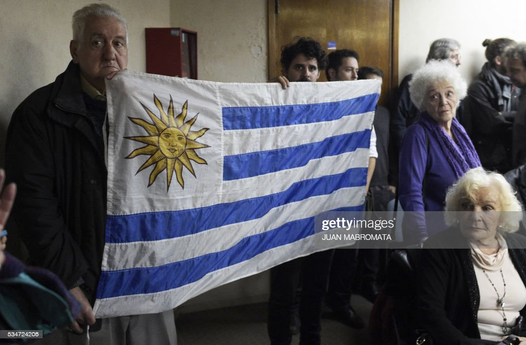 People hold an Uruguayan flag as they wait to hear the sentence to be handed down by the court in the trial on Operation Condor, in which six South American dictatorships collaborated to torture and kill their opponents, in Buenos Aires on May 27, 2016. South American ex-military leaders faced judgment Friday for their alleged role in the torture and assassination of leftist dissidents during a US-backed crackdown by the region's dictatorships during the 1970s and 1980s. Argentine judges were considering their verdict in the trial of 18 former army officers accused of taking part in 'Operation Condor.' In that scheme, the military regimes of Argentina, Bolivia, Brazil, Chile, Paraguay and Uruguay helped each other track down and kill leftist dissidents. / AFP / JUAN
