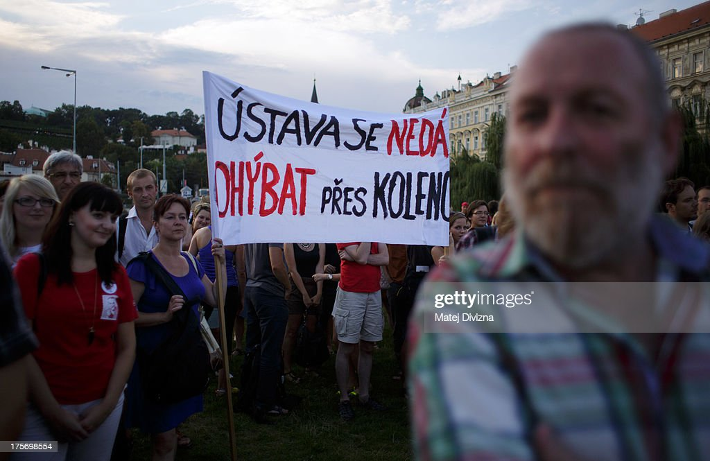 People hold banner and listen speech during the protest against the caretaker government of Czech Prime Minister Jiri Rusnok on August 6, 2013 in Prague, Czech Republic. Rusnok's caretaker cabinet, which Czech President Milos Zeman appointed July 10 despite protests from most political parties in the Czech Chamber of Deputies, will go through a vote of confidence in parliament tomorrow, August 7. Leaders of the former center-right coalition parties said they will not support Rusnok's government in tomorrow's vote.