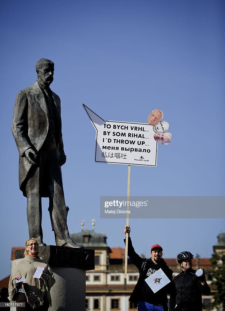 People hold banner that reads 'I'd throw up' in five languages and shows headshots of former Czech President Vaclav Klaus, Russian President Vladimir Putin and Czech President Milos Zeman as they stand under the statue of the first President of Czechoslovakia T. G. Masaryk during a protest against Czech President Milos Zeman on the Czech Statehood Day, September 28, 2013 in Prague, Czech Republic. Protest was for self-reflection of Milos Zeman and against threat of Russian influence and power.
