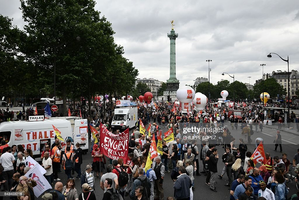 People hold banners and flags during a demonstration against controversial labour reforms, on June 28, 2016 on Bastille Square in Paris. Unions have called repeated strikes and marches in opposition to the law, which seeks to bring down France's intractable 10-percent unemployment rate by making it easier to hire and fire workers. / AFP / PHILIPPE