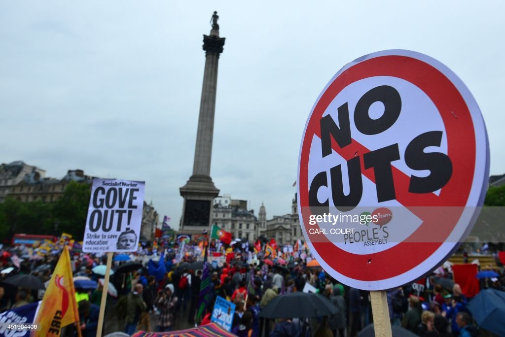 People hold banners and placards as they take part in a march and rally in central London on July 10 as more than one million public sector workers...