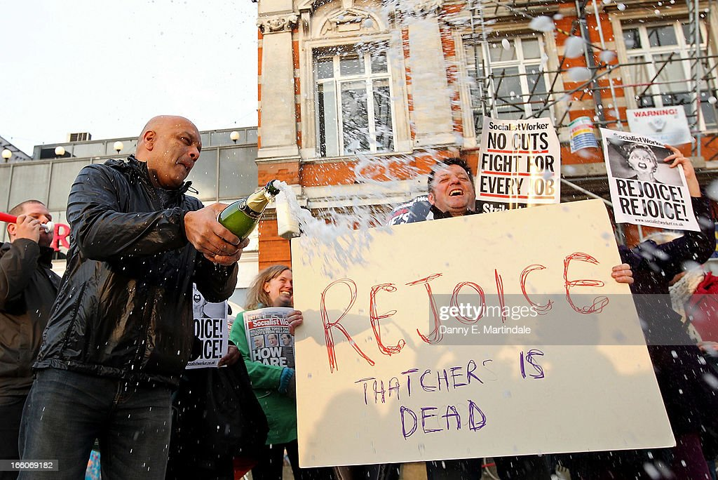 People hold banners and signs aloft as they celebrate the death of former British Prime Minister Margaret Thatcher in Brixton on April 8, 2013 in London, England. Lady Thatcher has died this morning following a stroke aged 87. Margaret Thatcher was the first female British Prime Minster and governed the UK from 1979 to 1990. She led the UK through some turbulent years and contentious issues including the Falklands War, the miners' strike and the Poll Tax riots.