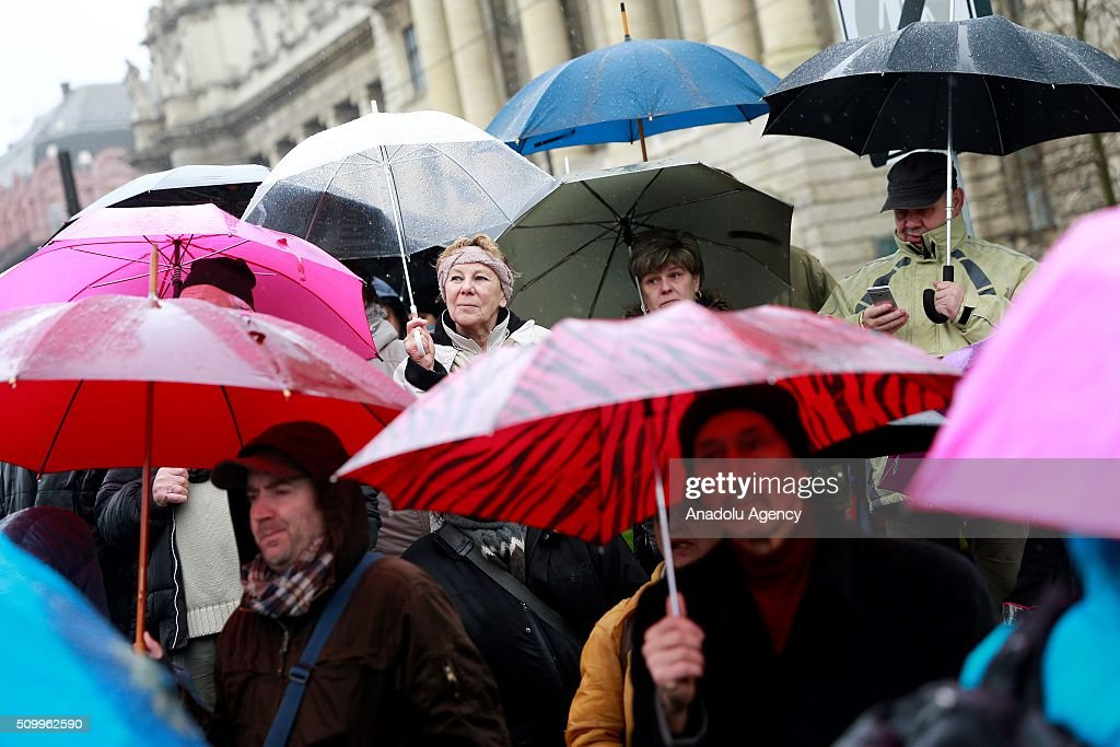 People hold banners and umbrellas as they demonstrate against the Hungarian government's education policies in front of the parliament building in Budapest, Hungary, on February 13, 2016.
