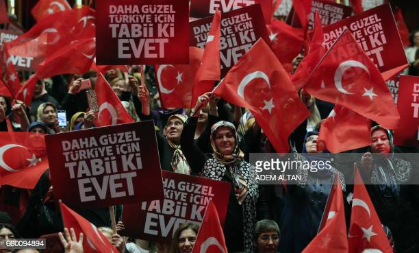 TOPSHOT People hold banners and wave Turkish flags during a meeting of Turkish President as part of the campaign for the constitutional referendum in...
