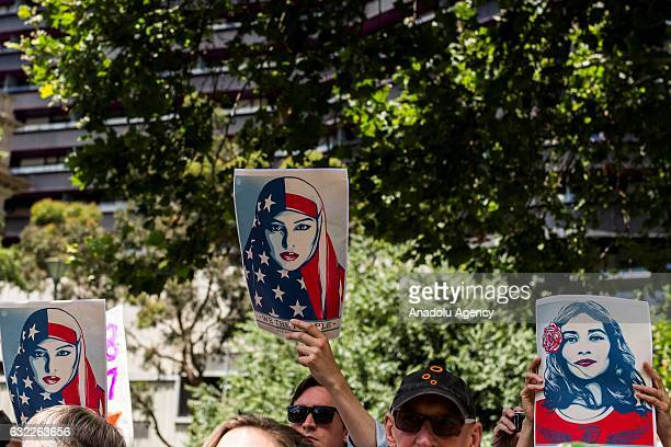 People hold banners as they gather for a rally protesting US new President Donald Trump following his inauguration on January 21 2017 in front of the...