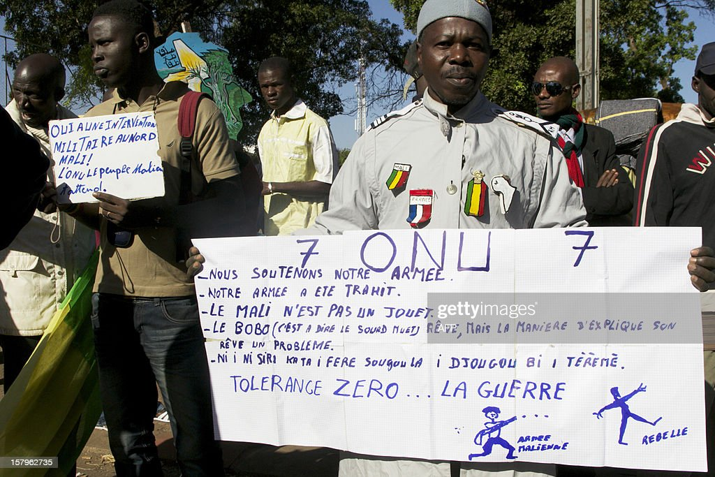 People hold banners as they join thousands of Malians in Bamako on December 8, 2012 to take part in a demonstration called by several Malian political parties to support the Malian army and demand a United Nations (UN) Security Council resolution approving the deployment of an international force in the country's north, controlled for eight months by Islamist armed groups. Facing the international community's equivocation on the matter, impatience rises in Mali's people, who say they are ready to go to war to take their 'own destiny in hand'.