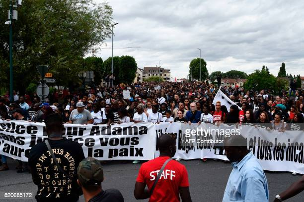 People hold banners as they take part in a march in memory of Adama Traore who died during his arrest by the police in July 2016 on July 22 2017 in...