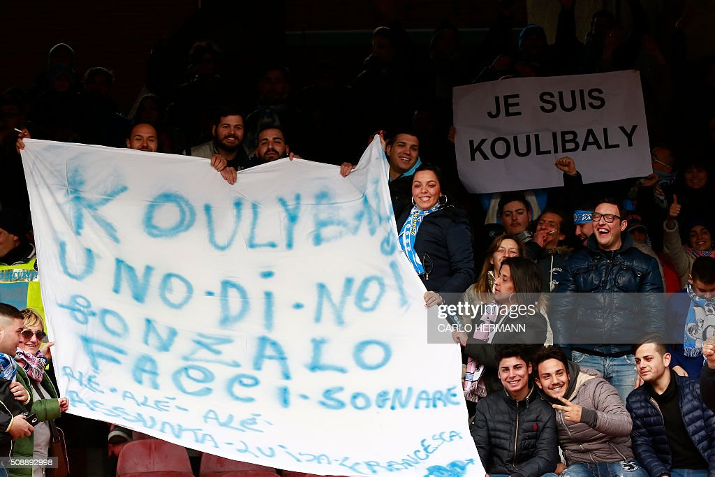 People hold banners diplaying the name of Napoli's French defender Kalidou Koulibaly before the Italian Serie A football match SSC Napoli vs Carpi FC on February 7, 2016 at the San Paolo stadium in Naples, in solidarity with the player victim of racists slogans from Lazio's fans during the football match SS Lazio vs SSC Napoli on February 3. / AFP / CARLO HERMANN