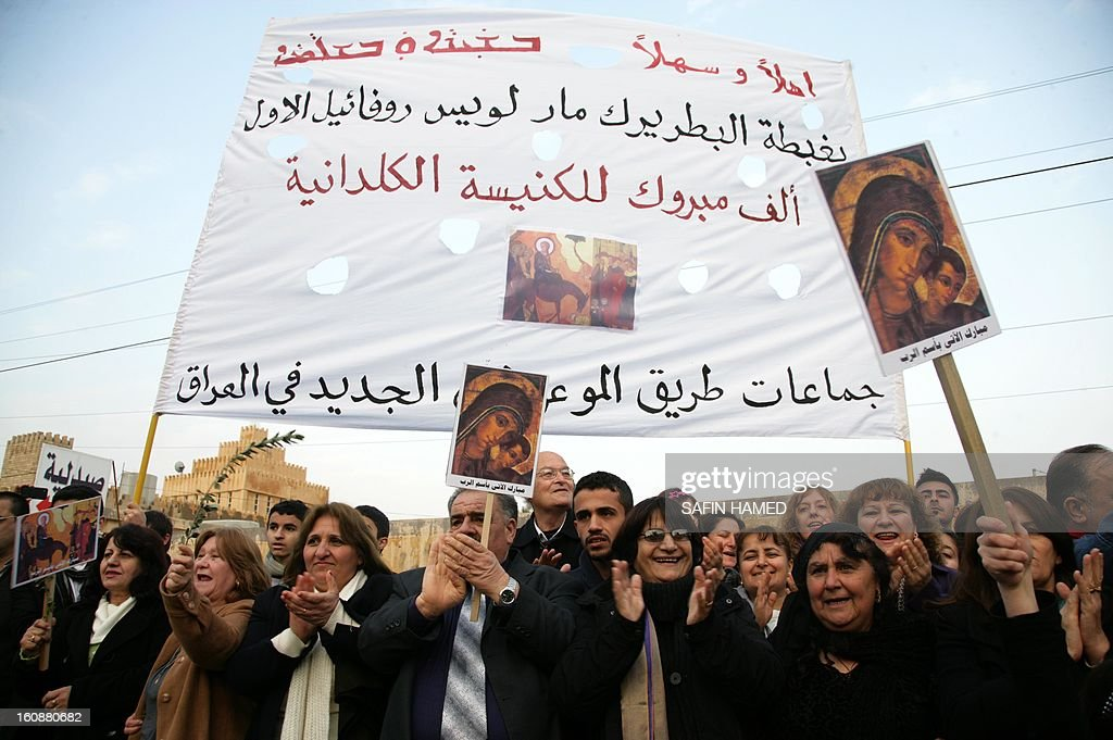 People hold banners during a ceremony marking the return to Iraq from the Vatican of the new patriarch of the Iraq-based Chaldean Church, Louis Sako, on February 7, 2013 at Saint Joseph's Cathedral in the northern Kurdish city of Ainkawa. Louis Sako, who replaced Emmanuel III Delly, will take the official title of Patriarch of Babylon of the Chaldeans.