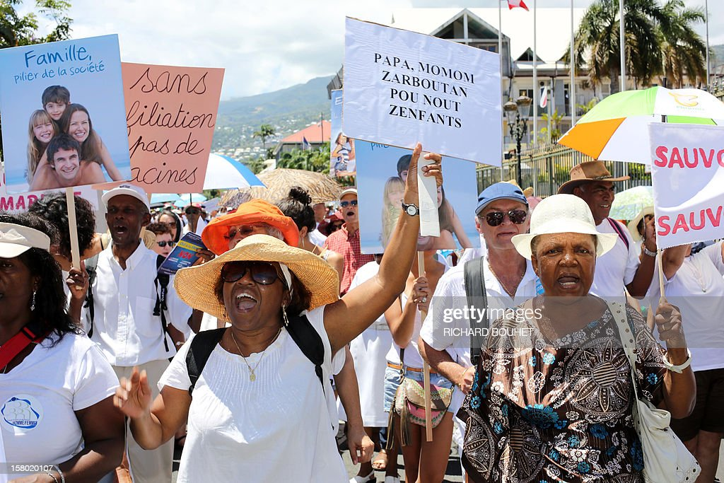 People hold banners during a demonstration called by a group of associations which support the same-sex marriage, on December 9, 2012, in Saint-Denis de la Reunion, on the French Indian Ocean island of La Reunion. France's Socialist government adopted on November 7, 2012 a draft law to authorise gay marriage and adoption despite fierce opposition from the Roman Catholic Church and the right-wing opposition. The board at left reads : 'The family is the pillar of the society'.