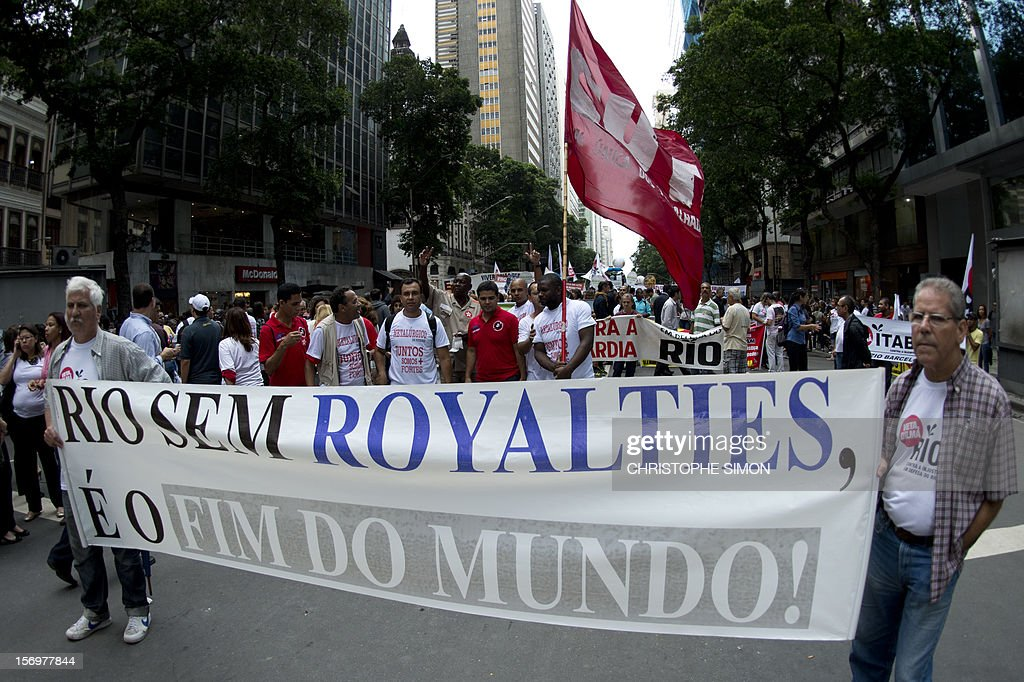 People hold banners during a demonstration demanding Brazilian President Dilma Roussef to veto a bill that would redistribute oil royalties in favor of non-oil producing states, in Rio de Janeiro, Brazil, on November 26, 2012. Both Rio de Janeiro's mayor Eduardo Paes and governor Sergio Cabral warned that the new oil royalties share-out plan will jeopardize the financing of the 2014 World Cup and the 2016 summer Olympics. AFP PHOTO/Christophe Simon
