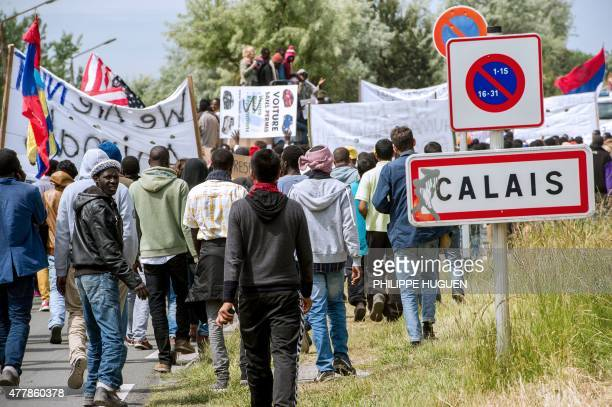 People hold banners during a demonstration of migrants in Calais northern France on World Refugee Day on June 20 2015 AFP PHOTO / PHILIPPE HUGUEN