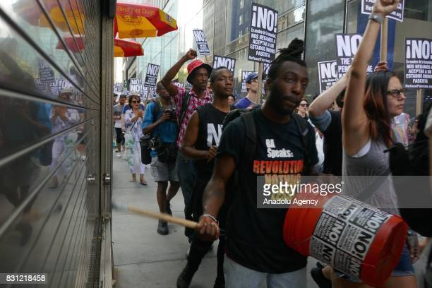 People hold banners during a protest in response to violence erupting at the white supremacist rally those organized by racist and nationalist groups...