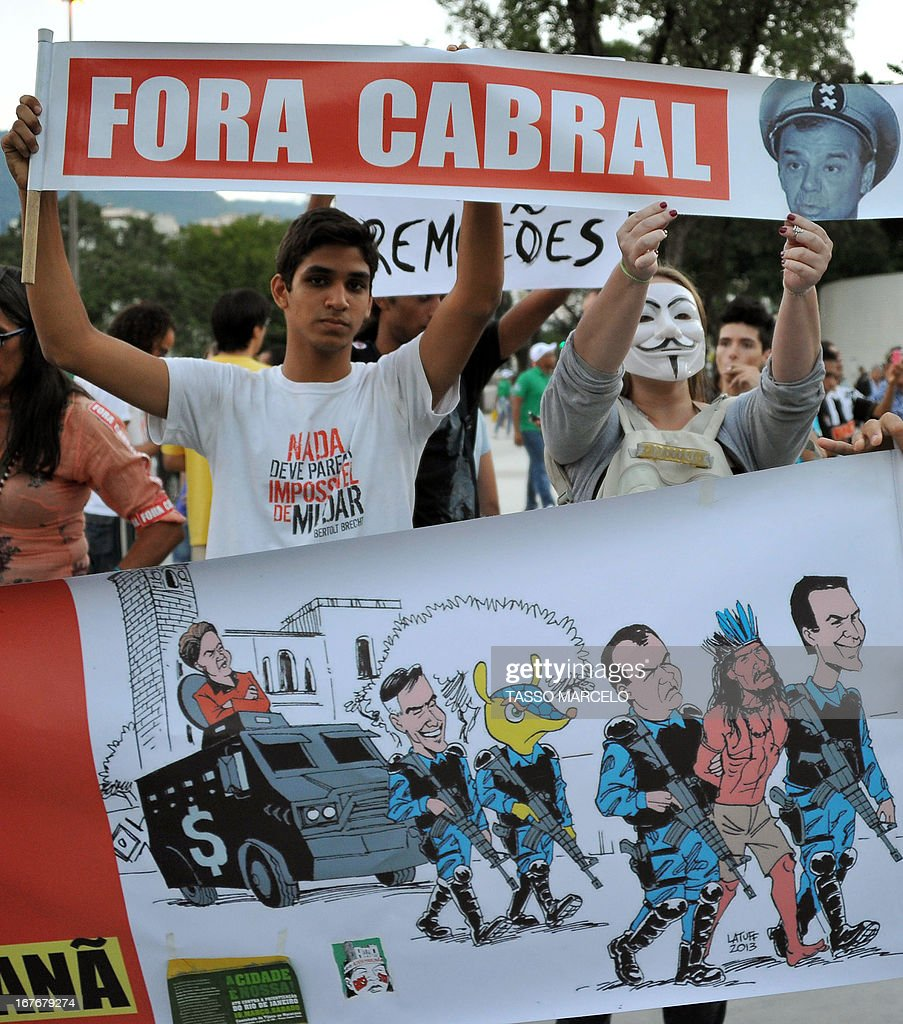 People hold banners during a protest outside the Mario Filho --Maracana-- stadium against its privatization and the demolition of the former Indigenous Museum, at the time that a test event is taking place in the Maracana stadium, in Rio de Janeiro on April 27, 2013. The Maracana will host the upcomig Confederations Cup --next June--, the Brazil 2014 FIFA World Cup and the 2016 Summer Olympics. AFP PHOTO / TASSO MARCELO