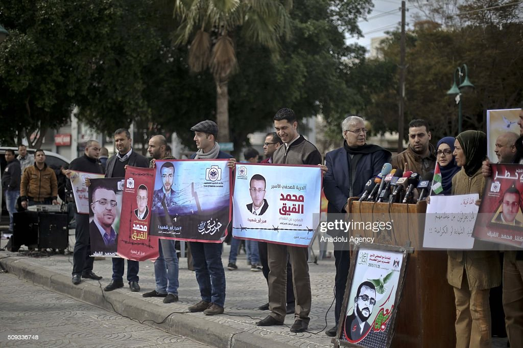 People hold banners of Palestinian journalist Mohammed al-Qiq who stages a hunger strike in Israeli prison, during a protest, demands to release of him at Monument of the Unknown Soldier in Gaza City, Gaza on February 10, 2016.
