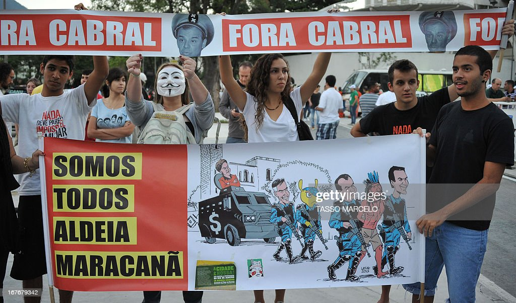 People hold banners outside the Mario Filho --Maracana-- stadium during a protest against its privatization and the demolition of the former Indigenous Museum, at the time that a test event is taking place inside the stadium, in Rio de Janeiro on April 27, 2013. The Maracana will host the upcomig Confederations Cup --next June--, the Brazil 2014 FIFA World Cup and the 2016 Summer Olympics.