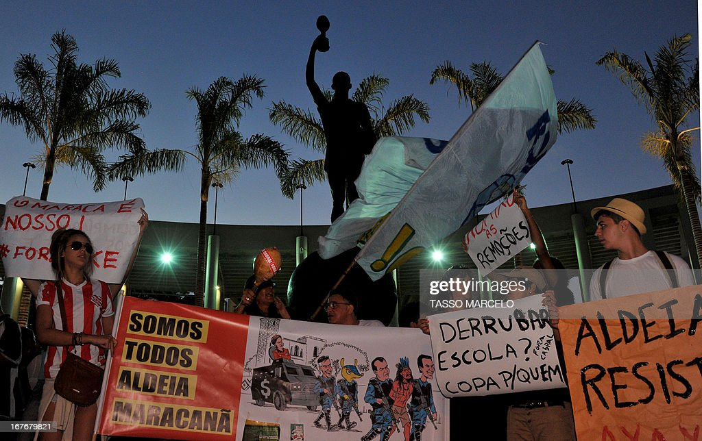 People hold banners outside the Mario Filho --Maracana-- stadium during a protest against Maracana's privatization and the demolition of the former Indigenous Museum, at the time that a test event is taking place inside, in Rio de Janeiro on April 27, 2013. The Maracana will host the upcomig Confederations Cup --next June--, the Brazil 2014 FIFA World Cup and the 2016 Summer Olympics.