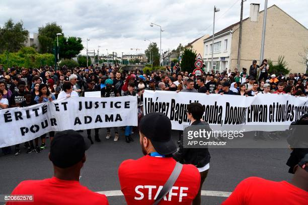 People hold banners reading 'Truth and Justice for Adama' as they take part in a march in memory of Adama Traore who died during his arrest by the...