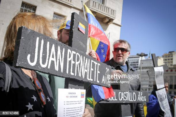 People hold banners to stage a demonstration while Foreign Ministers of Brazil Argentina Paraguay and Uruguay hold a meeting on South American trade...