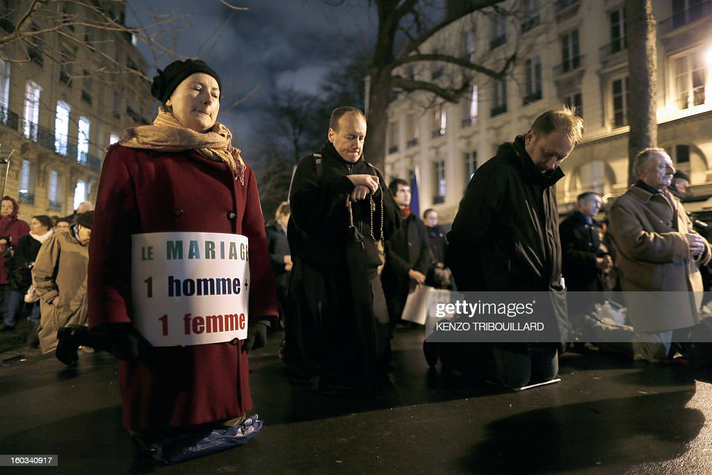 'Marriage = one men + one woman' as they pray during a protest organized by fundamentalist Christians group Civitas Institute against same-sex marriage on January 29, 2013 in Paris. France's parliament began today examining draft legislation on same-sex marriage after months of rancorous debate and huge street protests by both supporters and opponents. AFP PHOTO / KENZO TRIBOUILLARD