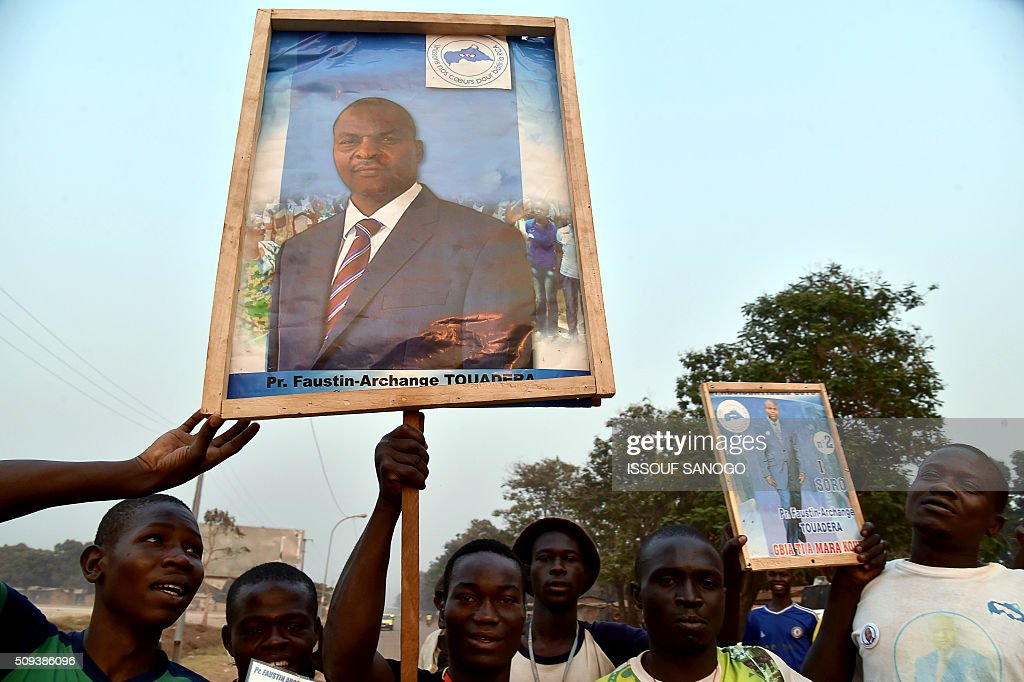 People hold campaign posters of Central African Republic second round presidential candidate Faustin Archange Touadera in Bangui on February 10, 2016, ahead of the Febuary 14 presidential and legislatives elections. The deferred presidential run-off, delayed due to organisational problems, and postponed legislative election, rescheduled after annulment due to irregularities, have been widely seen as turning a page on the worst sectarian violence in the traditionally unstable and dirt poor nation. / AFP / ISSOUF SANOGO