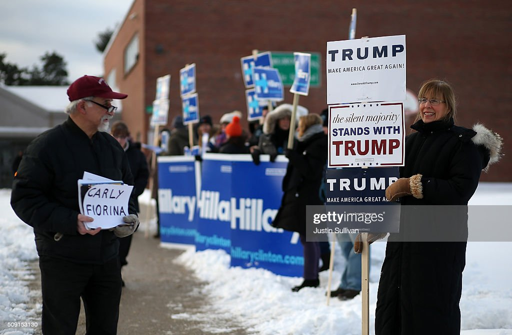 People hold campaign signs outside of a polling station at Fairgrounds Junior High School on February 9, 2016 in Nashua, New Hampshire. New Hampshire voters are heading to the polls in the nation's first primary elections.