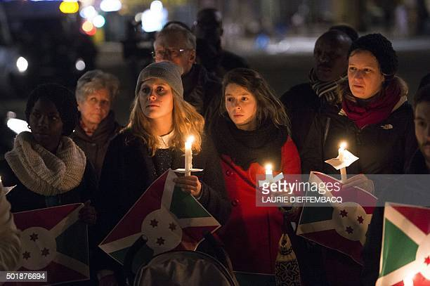 People hold candles and Burundian flags during a vigil to call for an end of the killings in Burundi on December 18 in Brussels Small destitute...