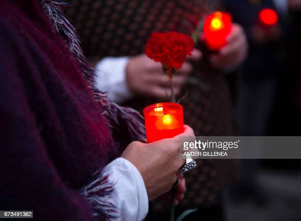 People hold candles and flowers during a ceremonial march to commemorate the 80th aniversary of the bombing the Spanish northern Basque village of...