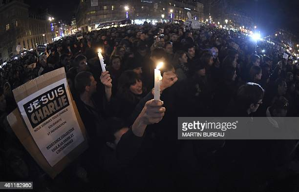 People hold candles and placard reading in French 'I am Charlie' during a gathering on the Place de Republique in Paris on January 8 in tribute to...
