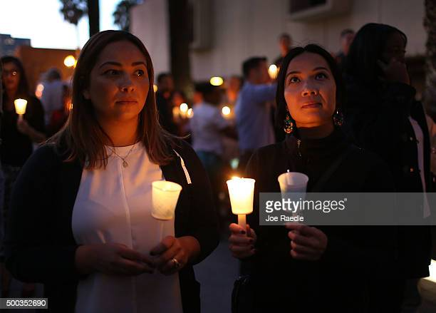 People hold candles as they attend a vigil held at the San Bernardino County Board of Supervisors headquarters to remember those injured and killed...