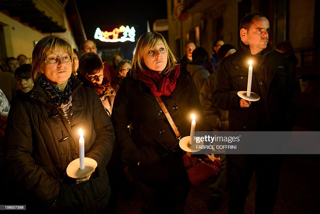 People hold candles as they pay their respects on January, 5, 2013 during a march in memory of the victims of a shooting in the village of Daillon. A gunman with psychiatric and drug problems killed three women and wounded two men on January 3, 2013 in a shooting spree in the tiny village where he lived in the mountains of southern Switzerland. Police shot and wounded the suspect after he threatened them with a gun following the attack in Daillon that raised fresh questions about the country's liberal gun ownership laws.