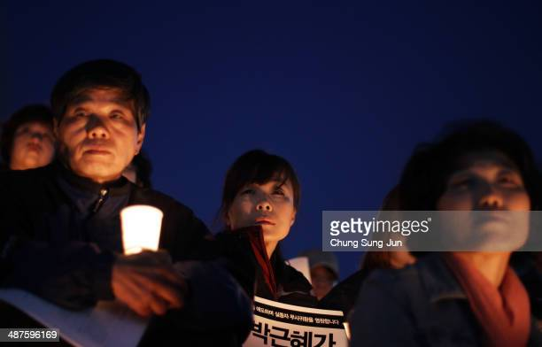 People hold candles as they pray for the safe return of missing passengers and tribute to the victims of the sunken ferry Sewol on May 1 2014 in...