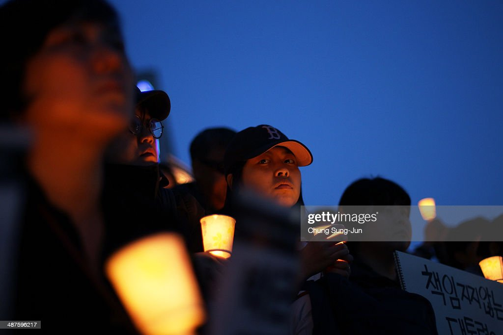 People hold candles as they pray for the safe return of missing passengers and tribute to the victims of the sunken ferry Sewol on May 1, 2014 in Seoul, South Korea. No survivors have been found since 174 passengers and crew were rescued on the day of the incident, April 16. South Korea's trade union, the Federation of Korean Trade Unions (FKTU) had announced cancellation of its annual May Day rally to mourn the ferry disaster victims.