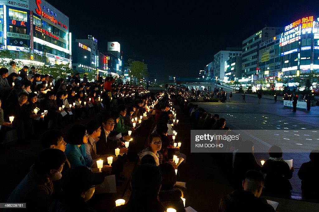 People hold candles at a vigil for students among the missing passengers of a South Korean capsized ferry, in central Ansan on April 22, 2014. The confirmed death toll from South Korea's ferry disaster passed 100 on April 22 as divers, under growing pressure from bereaved relatives, speeded up the grim task of recovering scores more bodies from the submerged ship. The banner at top translates to 'Rest in Peace'.