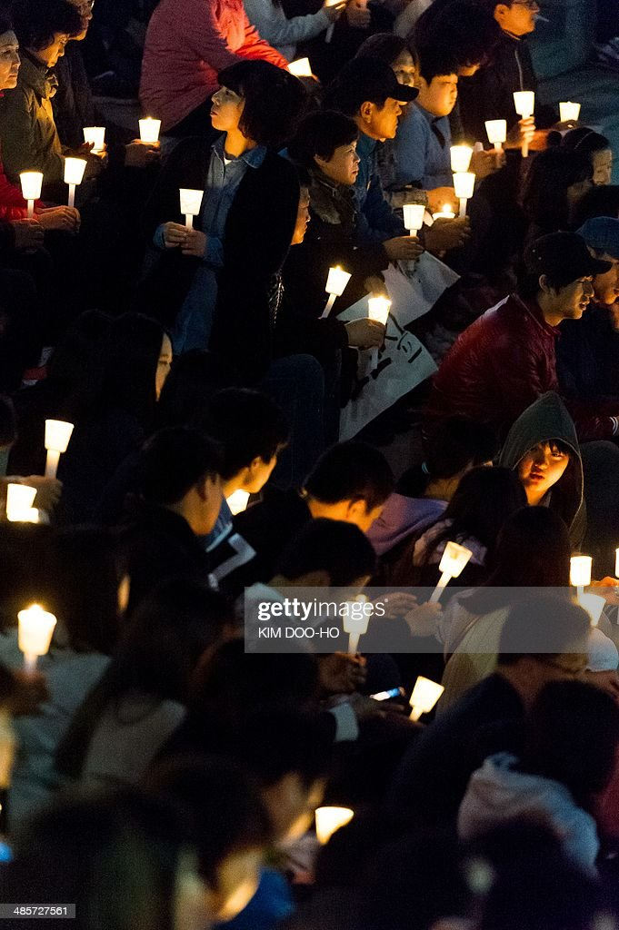 People hold candles at a vigil for the safe return of students among the missing passengers of a South Korean capsized ferry, in Ansan on April 20, 2014. Divers began to locate bodies on April 19 inside a submerged South Korean ferry as the detained captain defended his decision to delay evacuation of the ship when it capsized nearly four days ago with 476 people on board.