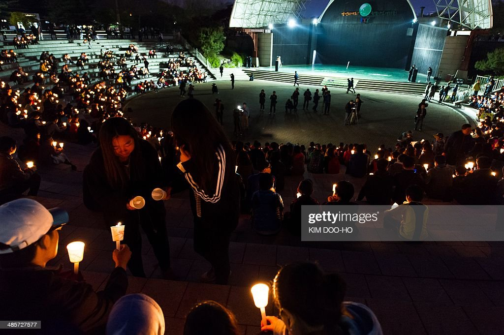 People hold candles at a vigil for the safe return of students among the missing passengers of a South Korean capsized ferry, in Ansan on April 20, 2014. Divers began to locate bodies on April 19 inside a submerged South Korean ferry as the detained captain defended his decision to delay evacuation of the ship when it capsized nearly four days ago with 476 people on board. AFP PHOTO / KIM DOO-HO