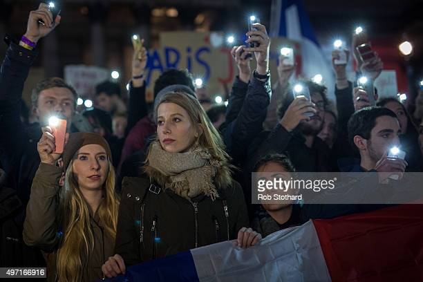 People hold candles at a vigil for victims of the Paris terrorist attacks in Trafalgar Square on November 14 2015 in London England Several landmarks...